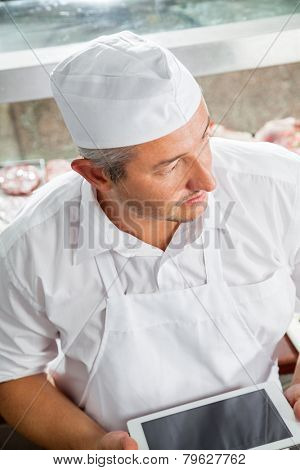 High angle view of happy butcher holding digital tablet in butchery
