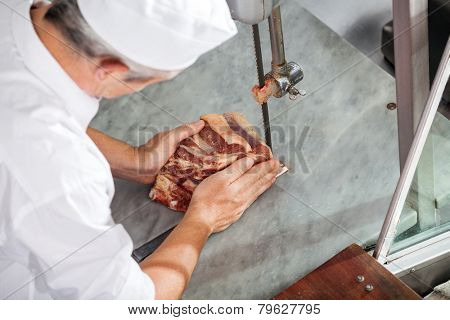 High angle view of butcher cutting fresh meat with bandsaw in butchery