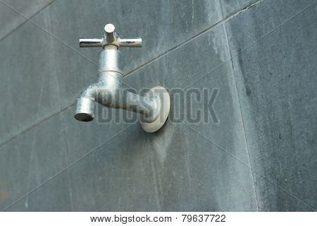 Faucet On A Gray Background At The Toilet