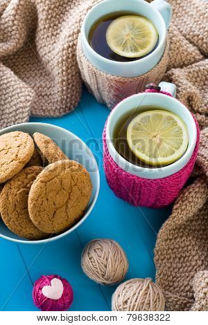 Two Blue Cup Of Tea In Knitted Sweater With Hearts Felt Standing Next To Tangle Bright Filaments And