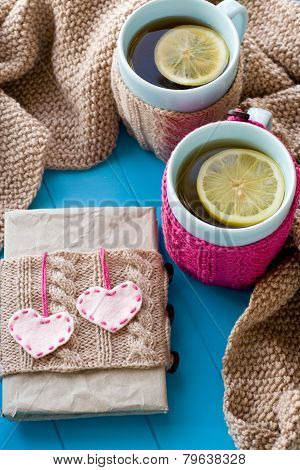 Two Blue Cup Of Tea In Knitted Sweater With Hearts Felt Standing Next To The Old Notebook And Blanke