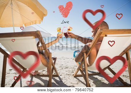 Happy couple clinking their glasses while relaxing on their deck chairs against love heart