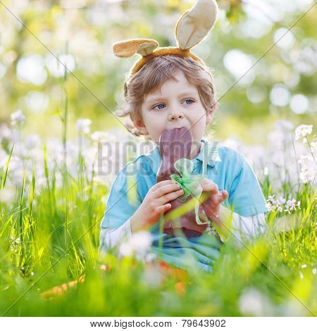 Little Child Wearing Easter Bunny Ears And Eating Chocolate At Spring Green Grass