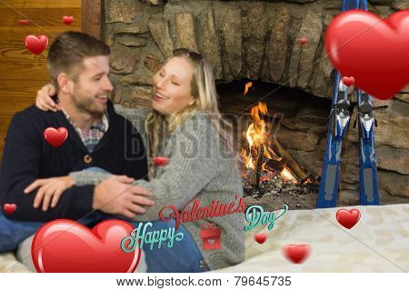 Cheerful couple with arms around in front of lit fireplace against happy valentines day