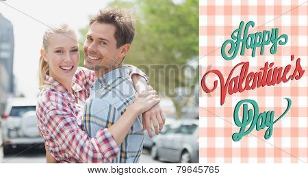 Couple in check shirts and denim hugging each other against happy valentines day