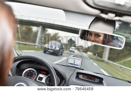 Woman in car binnacle looking at rear view mirror