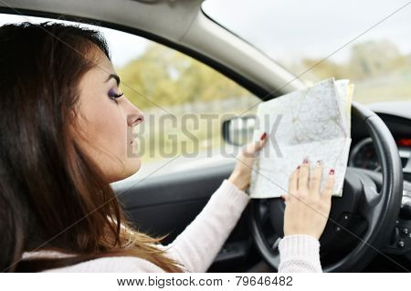Woman at steering wheel reading road map