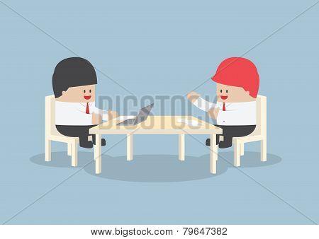 Businessmen Brainstorming Together At Conference Table