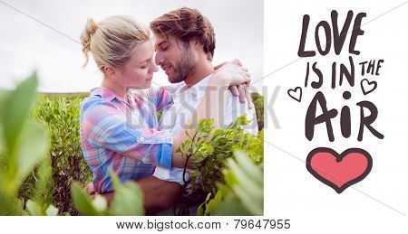Smiling couple embracing outside among the bushes against love is in the air