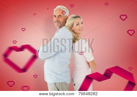 Smiling couple standing leaning backs together against red vignette
