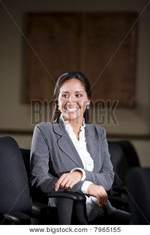 Hispanic Female Office Worker In Office Boardroom