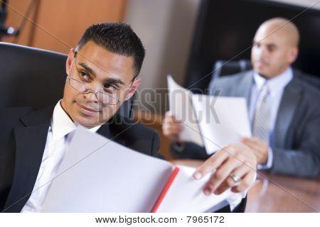 Hispanic Businessmen In Boardroom Reviewing Report