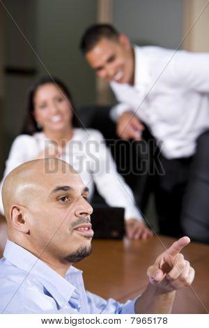 Hispanic Business People In Boardroom Watching