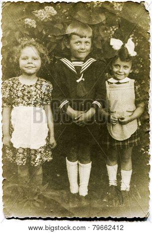 GERMANY, CIRCA THIRTIES: Vintage photo of three little children outdoor