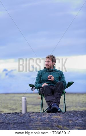 Camping man sitting in folding chair drinking coffee from thermos bottle flask at dusk in nature on Iceland. Camper relaxing thinking pensive taking break on road trip in beautiful Icelandic nature.