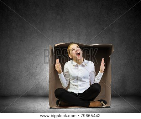Young businesswoman sitting in carton box and feeling uncomfortable