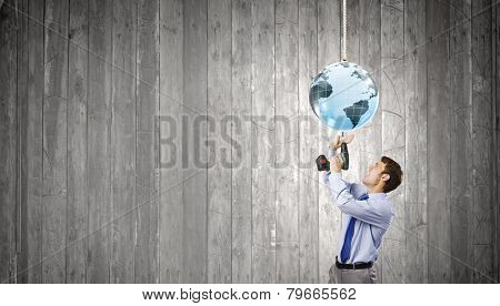 Young businessman tighten screw in to planet with drill