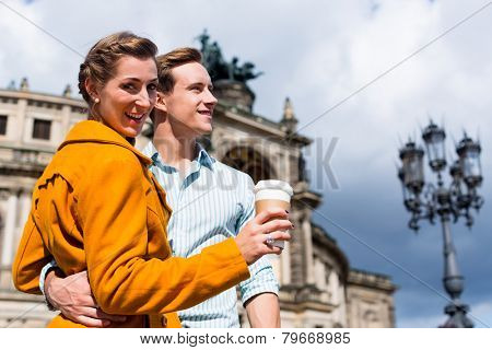 Tourist couple at Semperoper in Dresden having walk with coffee to takeaway
