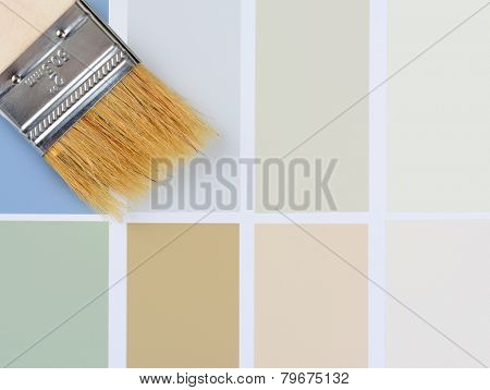 Closeup overhead shot of a paint brush laying on a color sample chart. Vertical format with the brush in the upper left corner, with copy space.