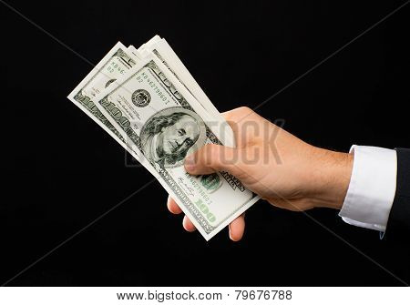 finances, people, savings and wealth concept - close up of male hands holding dollar cash money over black background