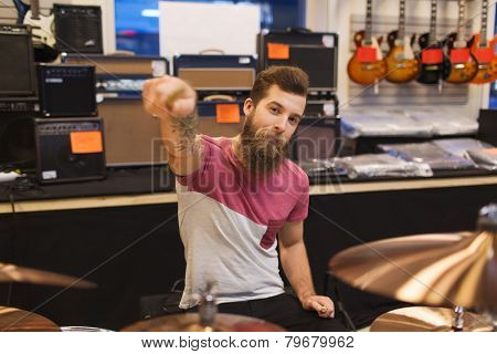 music, sale, people, musical instruments and entertainment concept - male musician playing cymbals and pointing drumstick to you at music store