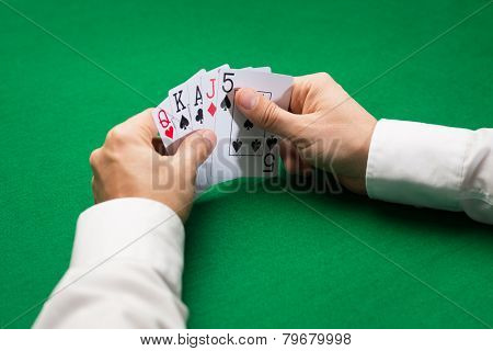 casino, gambling, poker, people and entertainment concept - close up of poker player holding playing cards at green casino table
