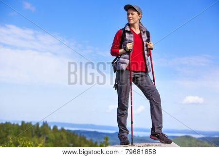 Young woman tourist standing on mountain top and looking aside.