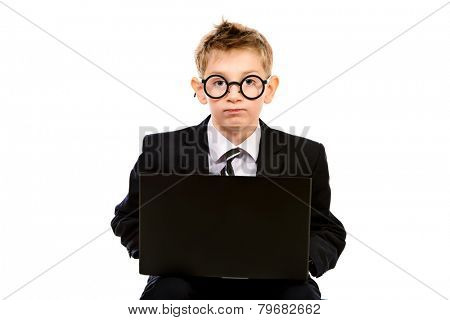Portrait of a smart boy in a suit and glasses sitting with his laptop. Profile. Isolated over white.