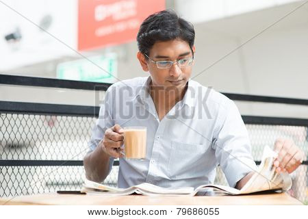 Asian Indian businessman reading newspaper while drinking a cup hot milk tea during lunch hour at cafeteria.
