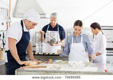 Male and female chefs making pasta together in commercial kitchen