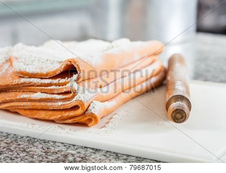 Closeup of flour on folded ravioli pasta sheets with rolling pin at countertop in commercial kitchen
