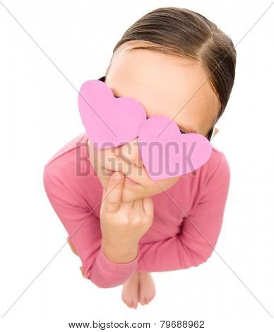 Little girl with hearts over her eyes, fisheye portrait, valentine concept, isolated on white