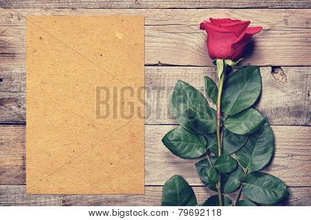 Vintage Rose And Blank Paper On Old Wooden Background