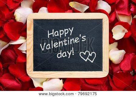 Happy Valentines Day! Text On Blackboard On Background Of Rose Petals
