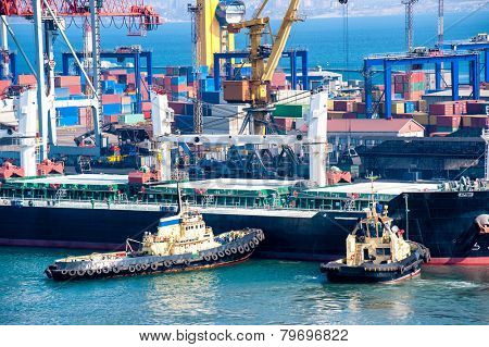 cargo ship and tug boat in industrial port