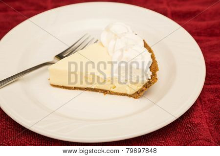 Slice Of Key Lime Pie On White Plate And Red Towel
