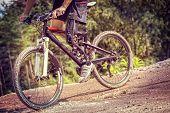 foto of prosthesis  - Shot of mountain bike rider with leg prosthesis riding downhill - JPG