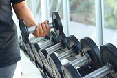 image of heavy  - strong women hand takes a heavy dumbbell in gym - JPG