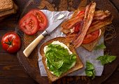 pic of tomato sandwich  - A delicious BLT bacon lettuce and tomato sandwich on rustic tabletop - JPG
