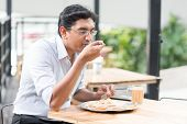picture of malaysian food  - Asian Indian business man eating food at cafeteria - JPG