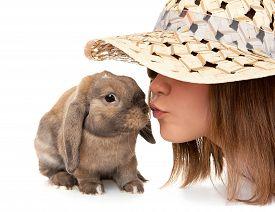 foto of dwarf rabbit  - Girl in a straw hat kisses dwarf rabbit - JPG
