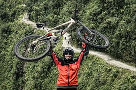 foto of biker  - Mountain biker pulls up his mountain bike at the famous downhill trail  - JPG