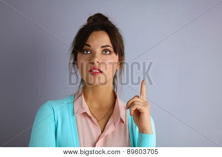 Portrait of an attractive fashionable young brunette woman pointing up