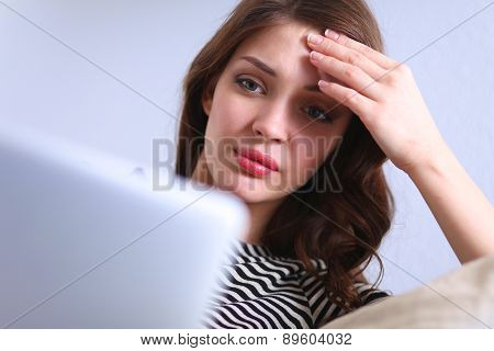 Portrait of a young woman sitting in front  her laptop on sofa