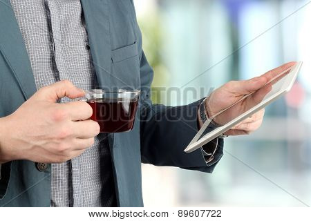 Image Of A Young Businessmen Standing In The Office  With Cup Of Coffee And Holding The Digital Tabl