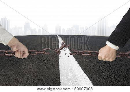 Businessman Pulling Rusty Iron Chains Broken With Asphalt Road Cityscape