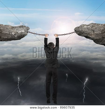 Businessman Hand Hanging Cracking Rusty Iron Chains Connect Two Cliffs