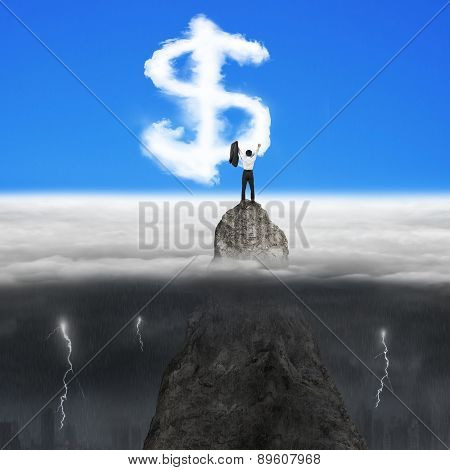 Businessman Cheering On Mountain Peak For Dollar Sign Shape Clouds