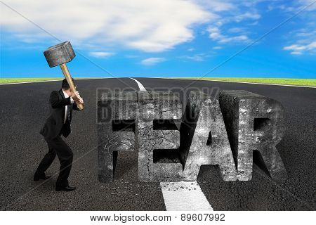 Businessman Holding Sledgehammer Hitting Fear Concrete Word On Asphalt Road