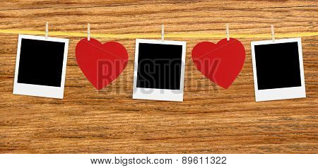 Vintage Photos Frame On The Clothesline With Hearts Over Wooden Background